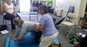 A woman doing a double hip squeeze at aMadriella Doula Workshop hosted by Corey Strouse