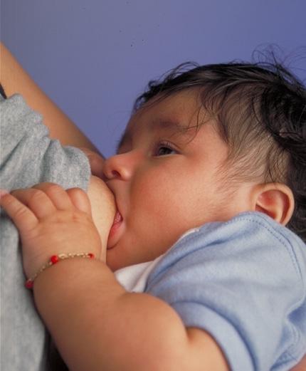 Photo: Breastfeeding infant, by Ken Hammond (Public Domain)