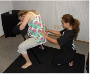 A Madriella student demonstrates how to massage the lower back while their client is sitting backwards in a chair.