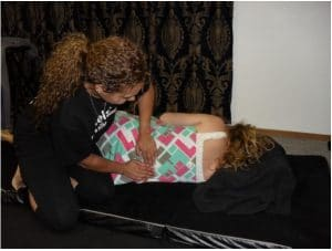 A Madriella student demonstrates how to massage the lower back in a side lying position