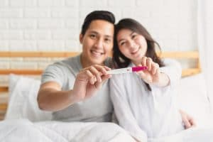 Happy couple showing the results of a pregnancy test