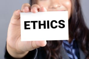 """woman holding a card that says """"Ethics"""""""