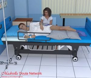 A Doula providing a back massage to a pregnant woman lying on her side in a hospital bed