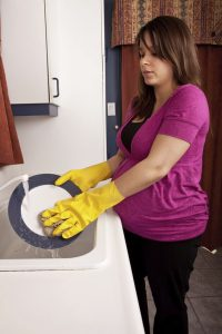 A young pregnant woman washing dishes