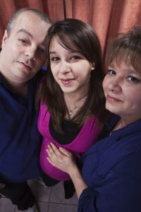 Parents supporting pregnant teenage daughter